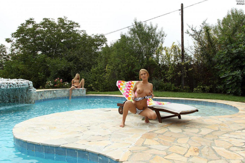 Кудрявая лесби Antonya седлает свою сожительницу страпоном на фоне бассейна